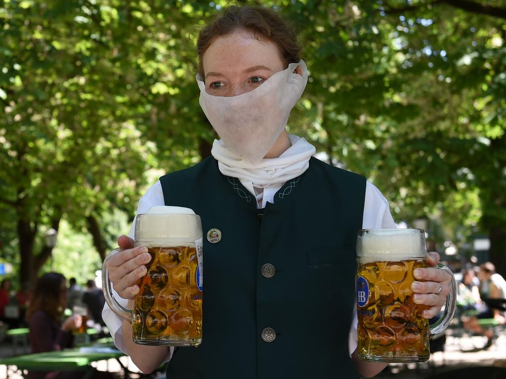 A waitress wears a protective mask and serves beer mugs in a beer garden in Munich. Picture: AFP