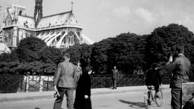 US soldiers walk outside Notre Dame in October 1944. The catherdral survived the war with bullet holes. Picture: AFP