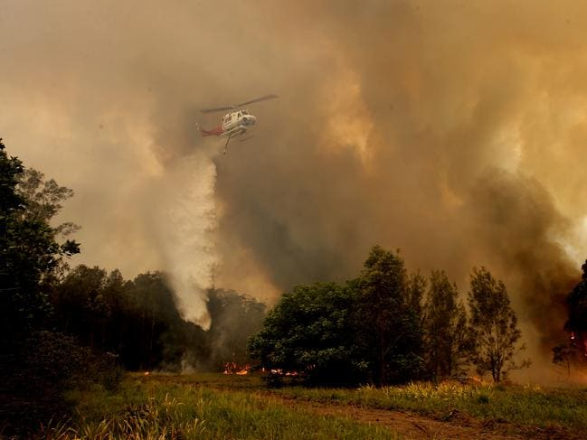 A fire bombing helicopter works to contain a bushfire along Old Bar road in Old Bar, NSW, Saturday, November 9, 2019. Two people have been killed and seven others are missing in bushfires in NSW which have also destroyed at least 100 homes. (AAP Image/Darren Pateman)