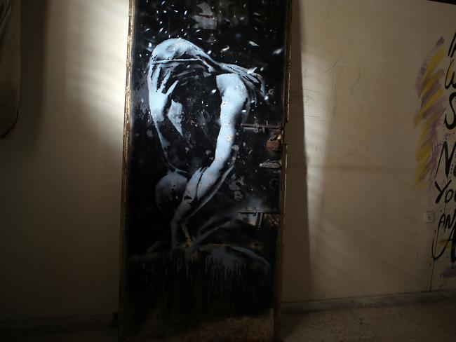 The mural of a weeping woman said to have been painted by British street artist Banksy, on the door of a house that was destroyed during the 50-day war between Israel and Hamas militants in the summer of 2014. Picture: AFP/SAID KHATIB