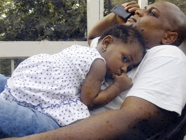 Died after travelling to Nigeria ... Patrick Sawyer, pictured with his daughter Ava at their home in Coon Rapids, had been in his native Liberia. (AP Photo)
