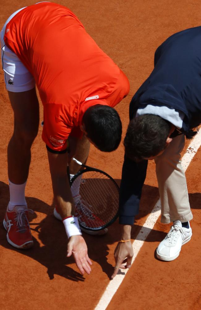 Novak Djokovic discusses a ball mark with the referee. (AP Photo/Pavel Golovkin)