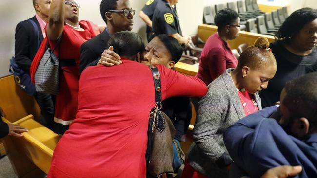 Members of Mr Jean's family embrace in the courtroom. Picture: Tom Fox/The Dallas Morning News via AP