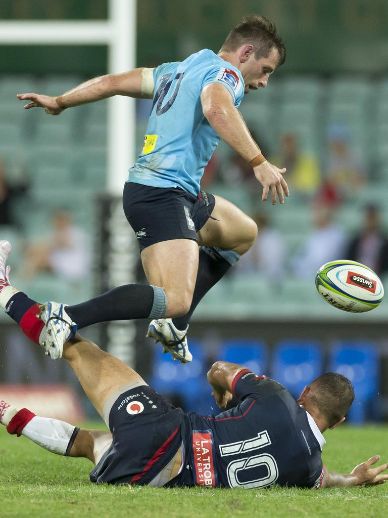 Bernard Foley of the Waratahs jumps Quade Cooper of the Rebels.