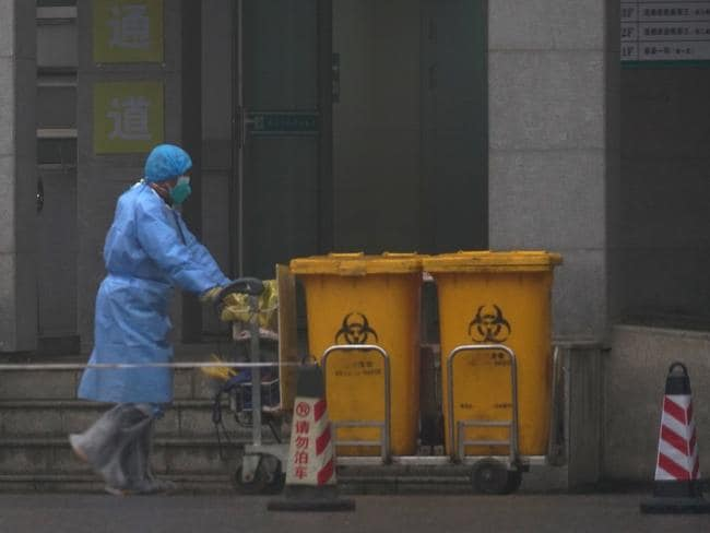 Staff move bio-waste containers past the entrance of the Wuhan Medical Treatment Center. Picture: AP