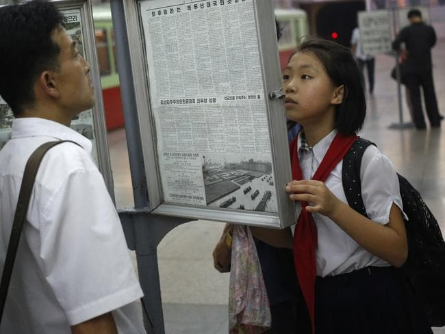 A young girl reads a public copy of the state-run daily newspaper at a subway station in the capital Pyongyang.