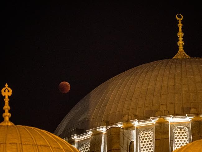 A total lunar eclipse is seen behind a dome of Istanbul's famous Suleymaniye Mosque. Picture: Chris McGrath