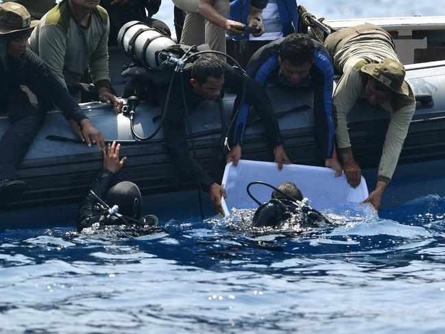 "Indonesian Navy divers try to put a ""black box"" into a plastic container after its discovery during search operations for the ill-fated Lion Air flight JT 610 at sea."