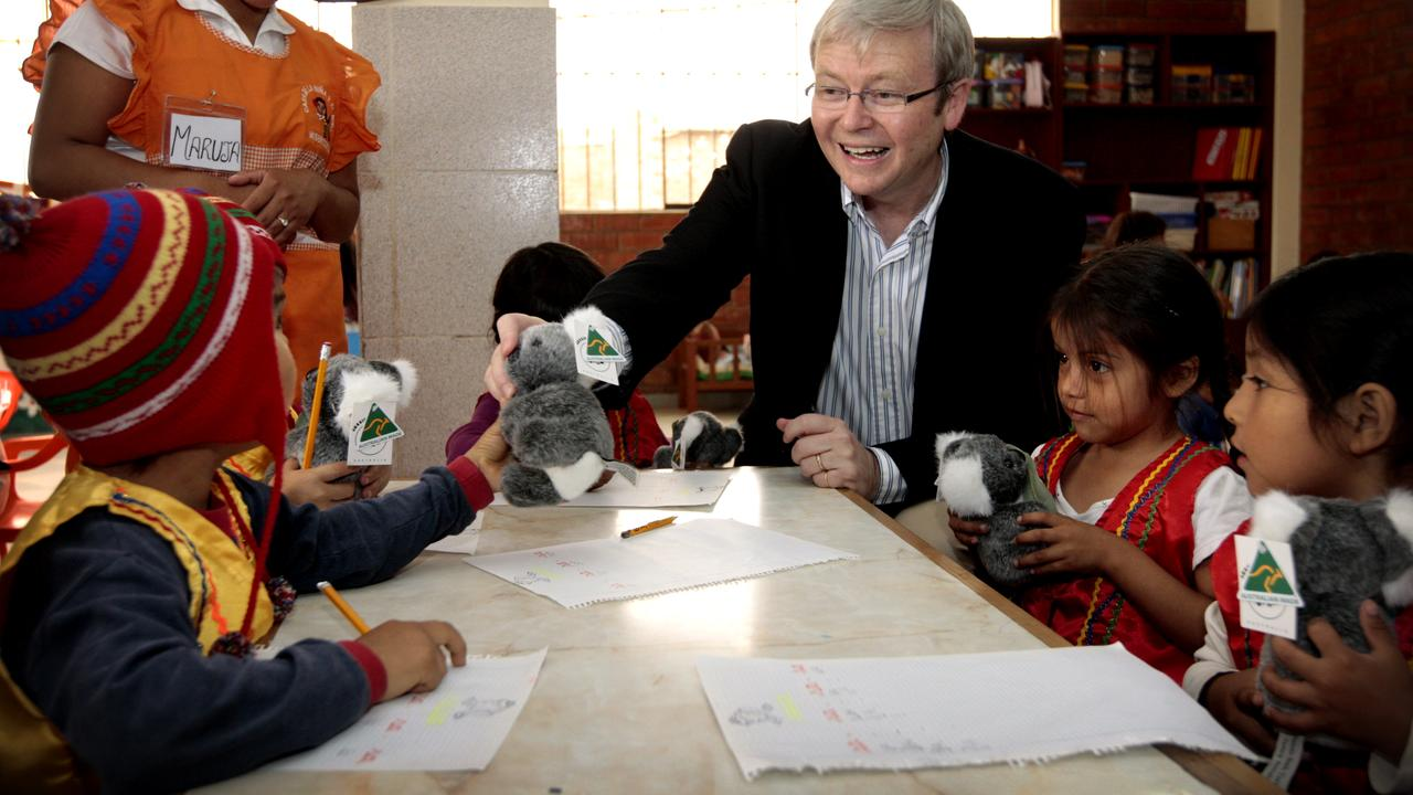Prime Minister Kevin Rudd giving out toy koalas to children at the Sisters of Mercy Family Health Service in Huandoy, Lima, Peru while attending the 2008 APEC Summit.