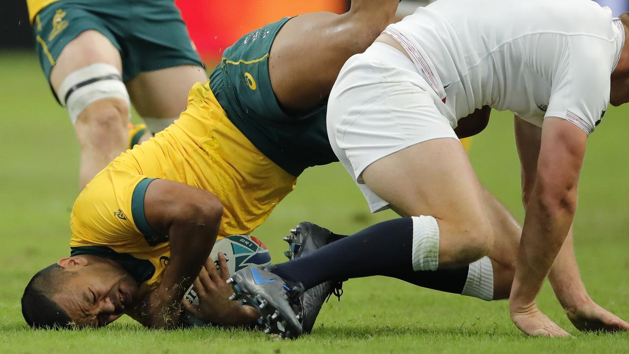 Australia's Kurtley Beale, left, falls off the field after being tackled by the England defense during the Rugby World Cup quarterfinal match at Oita Stadium in Oita, Japan, Saturday, Oct. 19, 2019. (AP Photo/Christophe Ena)