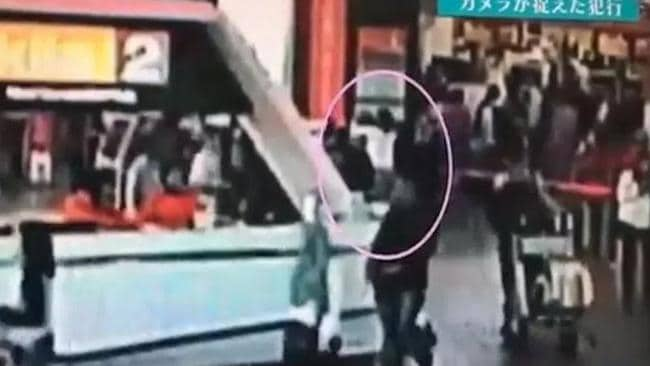 The moment: A woman white top creeps up behind Kim Jong-nam and appears to spray something in his face. Picture: Supplied