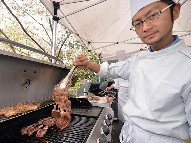 Feeling right at home ... A Japanese chef grills Australian beef and lamb chops for a reception hosted by visiting Australian Prime Minister Tony Abbott at the Australian embassy in Tokyo.