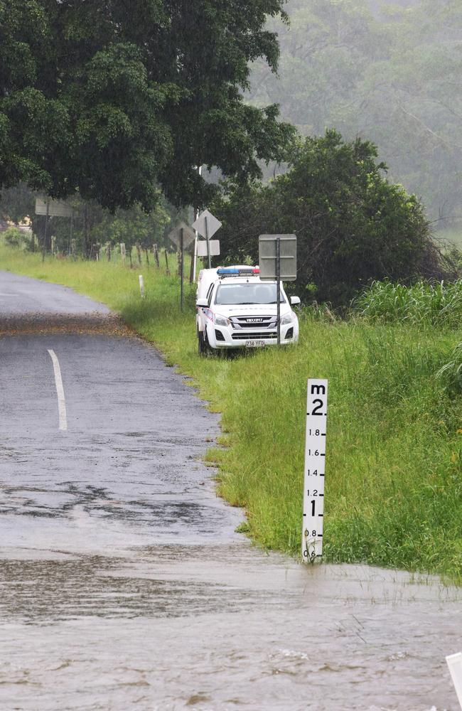 An abandoned police car sits on the other side of the water on Tallebudgera Creek Rd. Picture Glenn Hampson