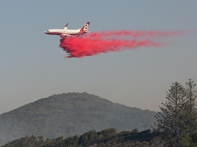 A water bombing plane drops fire retardant on a bushfire at Forster. Picture: Dan Kirkman, Something Visual/AAP