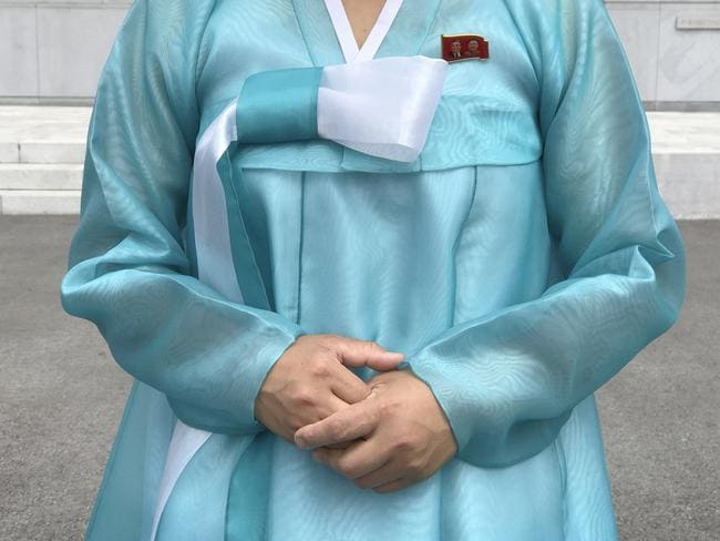 A factory guide in a traditional Korean dress with the faces of the late North Korean leaders Kim Il Sung and Kim Jong Il pinned above her heart on the left of her dress. Picture: Wong Maye-E/AP