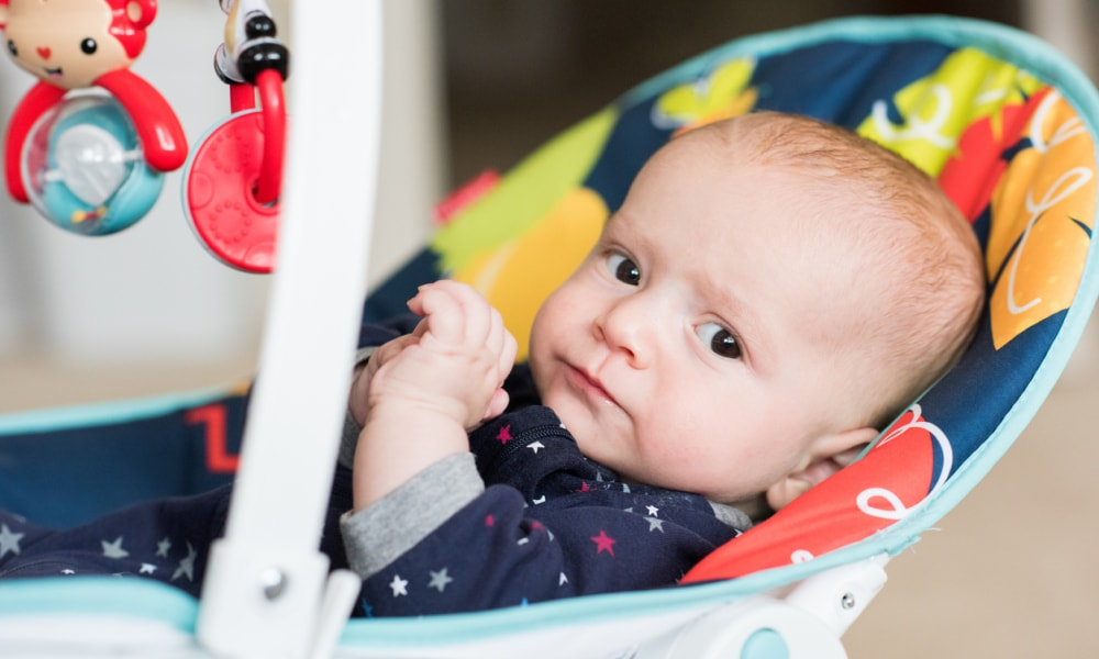 Infant boy looks at camera while resting in bouncing chair