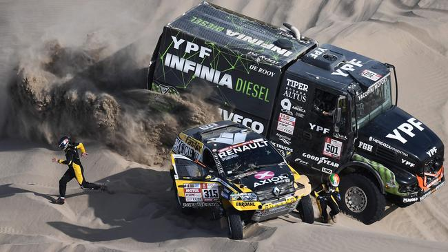Renault's Carlos Souza (R) and French co-driver Pascal Maimon run for safety as Iveco's truck driver Federico Villagra race past during Dakar Rally Stage 5.