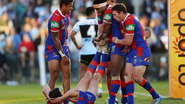 Newcastle players stretch a cramping Jarrod Mullen after the star five-eighth scored a try. Pic Brett Costello