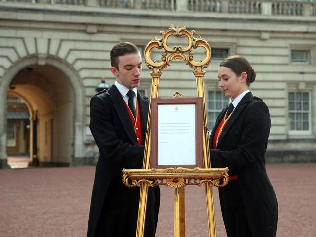 Footmen Stephen Kelly and Sarah Thompson set up the official notice on an easel at the gates of Buckingham Palace. Picture: AFP