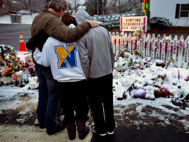 Members of the Rutter family of Sandy Hook, Connecticut embrace as they stand near memorials by the Sandy Hook firehouse. Picture: AP