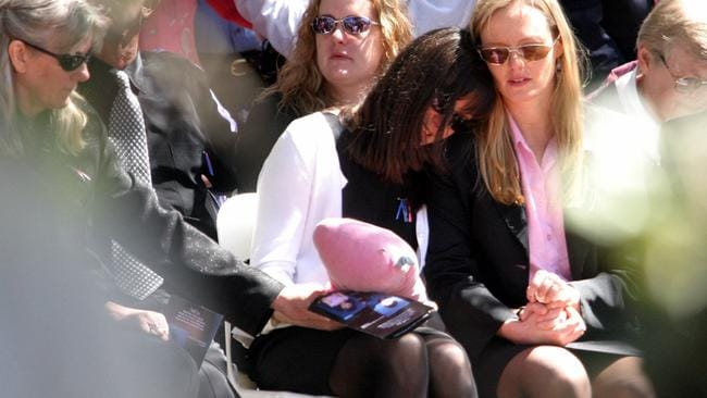 Ingrid Poulson is comforted at the funeral of her father, Peter Poulson, and her children Sebastian and Marilyn Kongsom, in 2003. Picture: Scott Hornby.