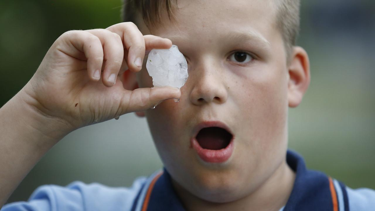 Cooper 10, holds one of the large hail stones that pelted down in Templestowe, Victoria in 2017. Picture: David Caird