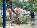 Locals Jayden Thacknay, 20; Raih Woodley, 22; and Rasa Lackey, 20; removing fallen branches from the main street of Airlie Beach as the eye of cyclone Debbie passed over. Photographer: Liam Kidston