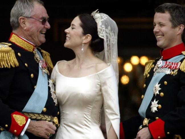 Crown Princess Mary laughs with her father-in-law Prince Henrik of Denmark as Crown Prince Frederik looks on after their wedding in 2004. Picture: Ian Waldie/Getty Images
