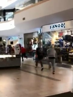 The group of men flee the scene, running through the shopping centre before one is caught.