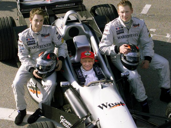 Niki Lauda sitting in McLaren Mercedes alongside his sons, Mathias, left, and Lukas, right.