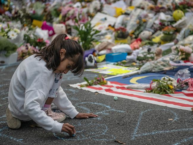 A young girl writes a message on the ground with chalk next to flowers and tributes near Al Noor mosque. picture: Getty Images