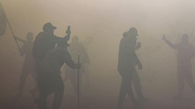 Iraqi supporters and members of the Hashed al-Shaabi military network can be seen through thick tear gas. Picture: Ahmad Al-Rubaye/AFP