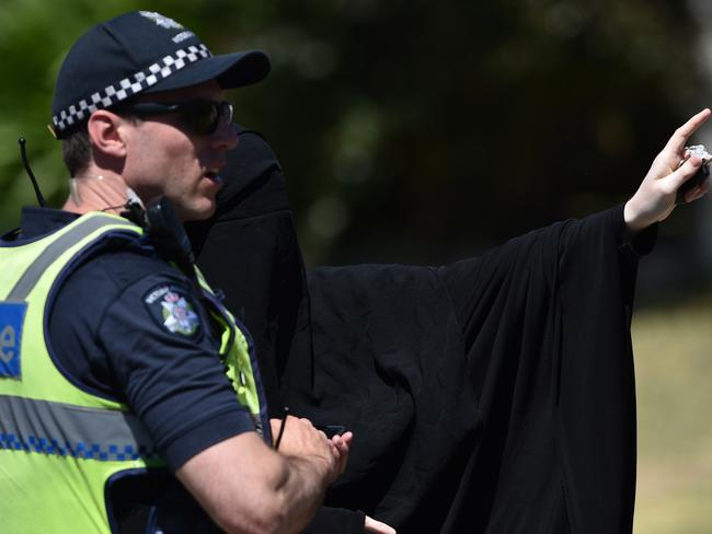 A women wearing a niqab speaks to police near a Meadow Heights property. Picture: Julian Smith/AAP
