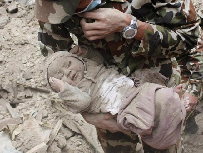 In this Sunday, April 26, 2015, photo taken by Amul Thapa and provided by KathmanduToday.com, four-month-old baby boy Sonit Awal is held up by Nepalese Army soldiers after being rescued from the rubble of his house in Bhaktapur, Nepal. Picture: Amul Thapa/KathmanduToday.com via AP