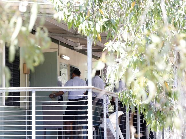 Staff from Serco wait at the door of a secure apartment at Mercure Hotel in Darwin before moving the Tamil family back to airport. Picture: Darrian Traynor/Getty Images.