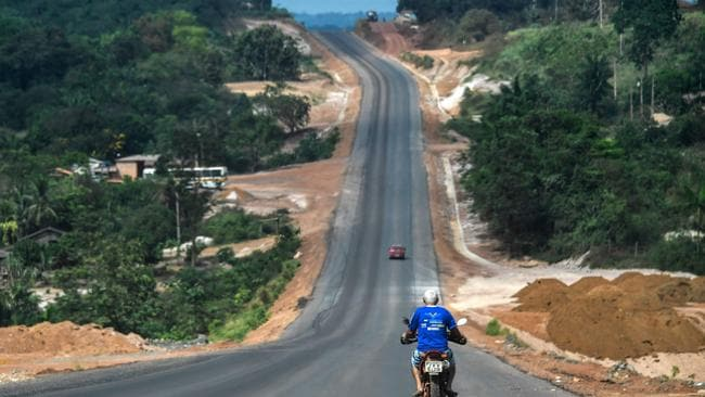 A motorcycle rides along the Trans-Amazonian highway (BR230) near Ruropolis. The route has played a key part in opening up once impenetrable parts of the Amazon, but at what cost? (Photo by Nelson Almeida/ AFP)