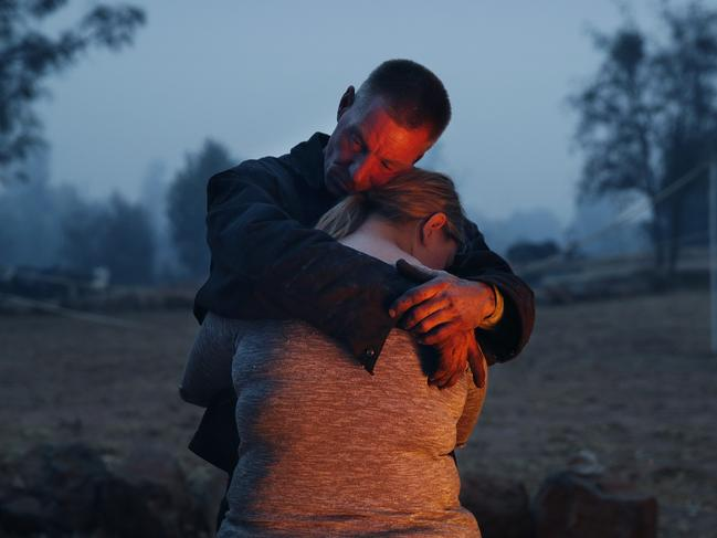 Phillip Harvey embraces his daughter Arianne Harvey as they stay warm beside a fire in Paradise, California. Picture: AP