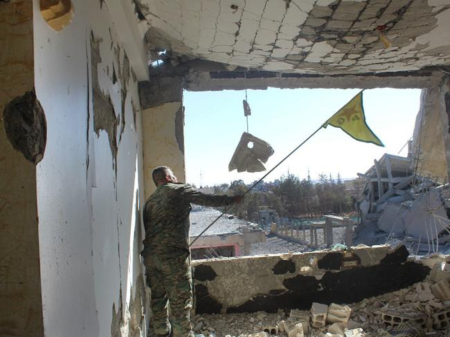 A Syrian Democratic Forces (SDF) fighter waves his Kurdish party flag at the front line where they battled against the Islamic State militants, in Raqqa. Picture: AP