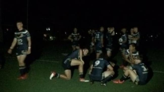 Cowboys players sit on the field in the dark after a blackout hit Cairns prior to kick-off.