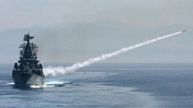 """Escalation ... The guided missile cruiser """"Moskva"""", shown here firing a missile fire during r combat training, has been deployed to the Syria-Turkey border to 'protect Russian aircraft'. Source: AFP"""
