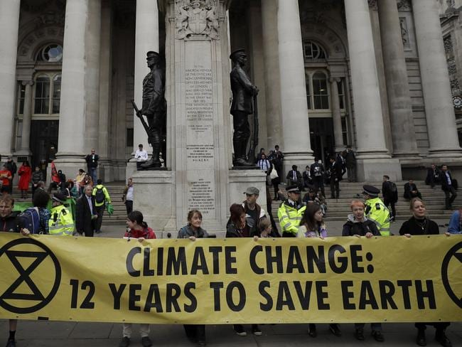 In this Thursday, April 25, 2019 file photo, Extinction Rebellion climate change protesters hold up a banner near the Bank of England, in the City of London. Picture: AP