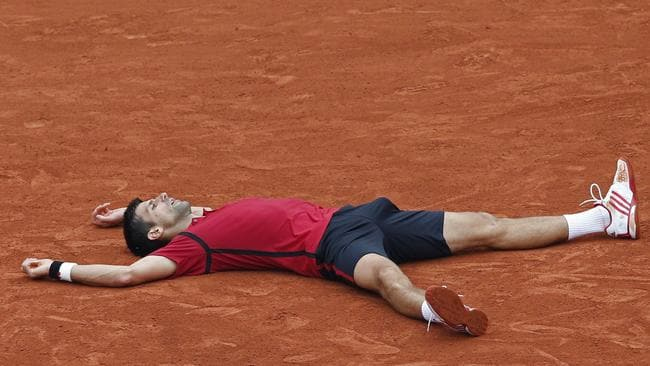 Novak Djokovic drops to the clay after winning match point.
