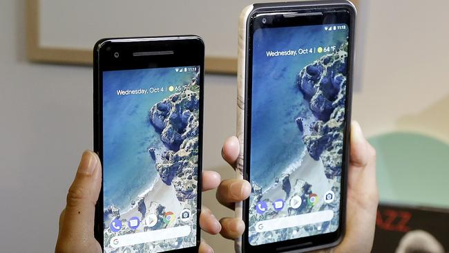 A woman holds up the Google Pixel 2 phone, left, next to the Pixel 2 XL phone at a Google event at the SFJAZZ Center in San Francisco. Picture: AP Photo/Jeff Chiu