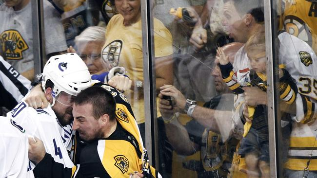 Vancouver Canucks defenseman Keith Ballard (4) and Boston Bruins left wing Brad Marchand (63) fight in 2011.