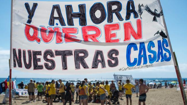 """A banner reading """"And now they want our houses"""" on La Barceloneta beach during anti-tourism protests on August 12, 2017. Picture: AFP/ Josep Lago."""