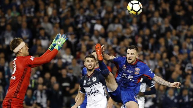 Newcastle Jets striker Roy O'Donovan goes up for the ball as Melbourne Victory goalkeeper Lawrence Thomas comes out to claim it. Picture: Toby Zerna