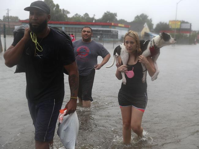 Naomi Coto carries Simba on her shoulders as they evacuate their home after the area was inundated with flooding. Picture: Getty/AFP