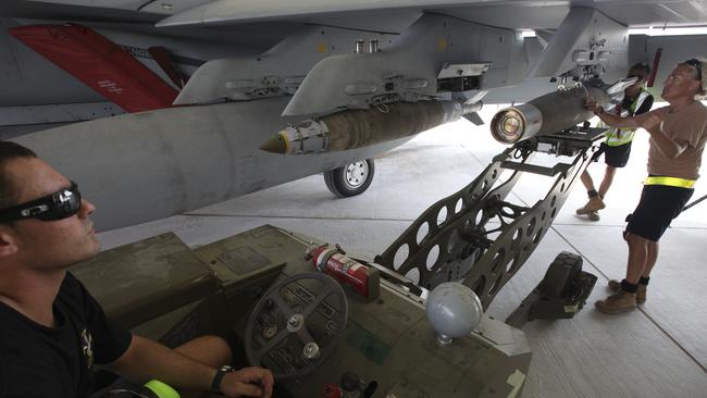 Delicate work ... Leading Aircraftman Josh Lees, guided by Corporal Kim Cooper, load explosive ordnance on to a Super Hornet in the Middle East.