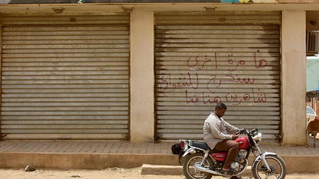 Arabic writing on the shutters of the closed shop reads: 'Another time, we shall take to the streets, crying out our demands loudly'. Picture: AFP