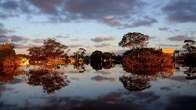 The sun rises over flooded streets in Bundaberg. Pic: Getty Images